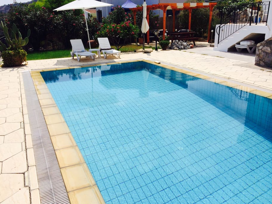 pool- with sun loungers and large pool umbrella.