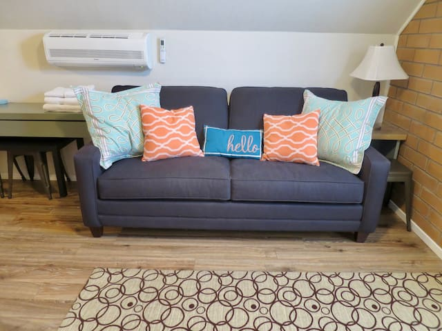 Convertible sofa bed.  Will provide linens and pillows for the bed upon request. There's a separate AC unit for this room with adjustable thermostat for guests' comfort.  A long black coffee table and stools are tucked under the desk.