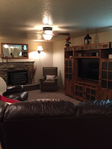 Living Room- Smart TV and Sofa Bed. Ceiling fan and fireplace.  Two chairs and ottoman.