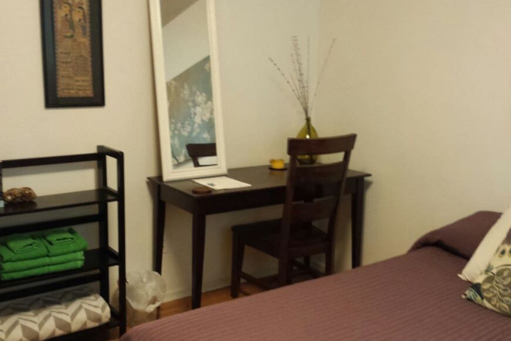 Book shelves,towel set, mirror, desk and chair add to the rooms comfort and function.