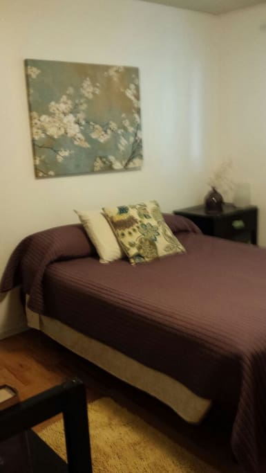 Comfortable double bed with a variety of pillows and bedside nightstand with lamp.