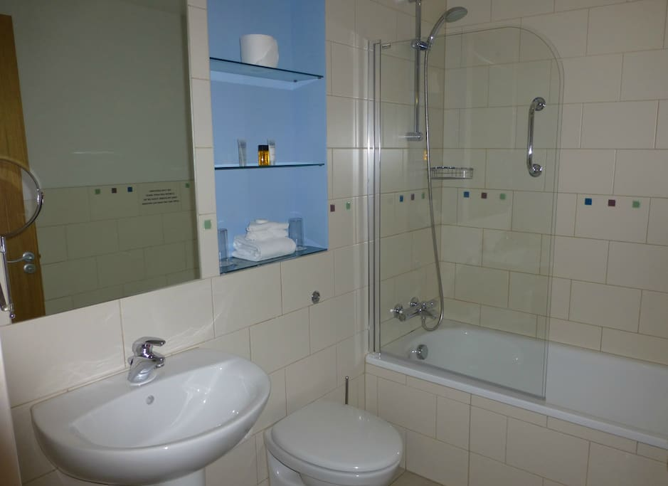 Large bathroom with shower over bath. The apartment has it's own hot water tank.