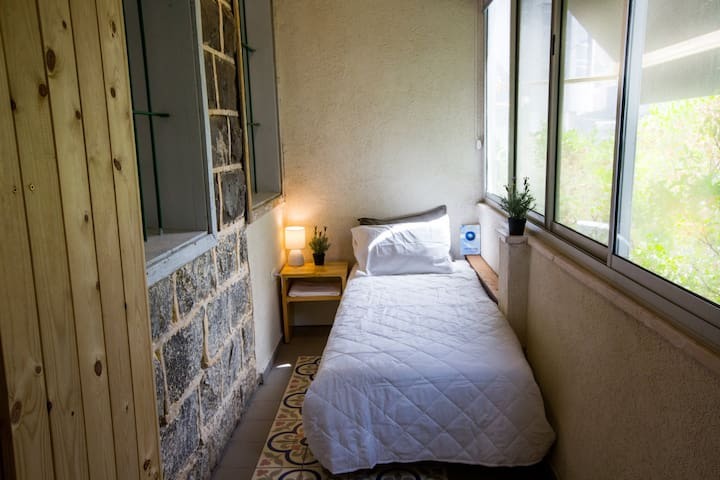 Single bed with view to Tiberias old neighbourhood. A curtain closes the room for privacy.