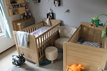 Toddler room with adjustable beds suitable for 5 year olds and under. Comfortable chair for story time.