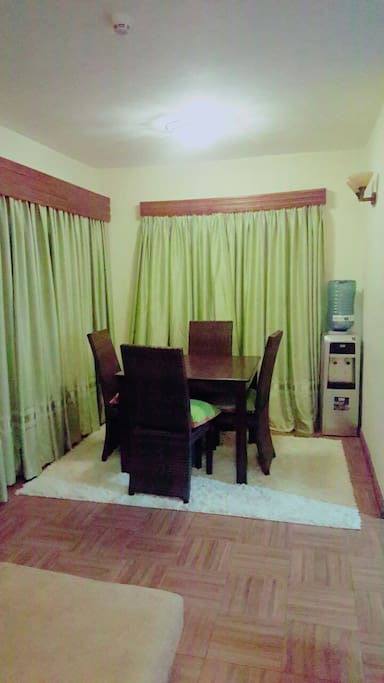 The dinning Area With Filled up water Dispenser Which provides both hot and cold water. Dining table