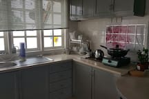 This is little kitchen with 2 door fridge, kettle,single gas stove,frying pan and pot. Plate etc enough for 4 pax(st least each one 1 set each of plate,bowl,spoon and fork. Dishwash and water filter also available