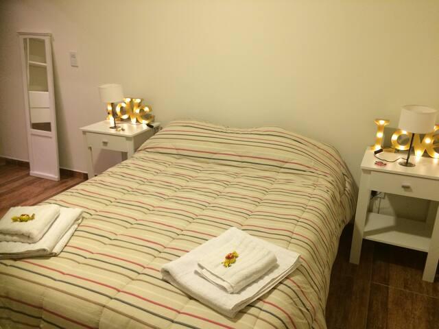 Habitacion con cama matrimonial y vestidor.