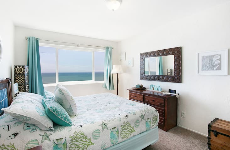 Master bedroom with the most amazing view . This beauty sits on the bluff in North Beach  over looking the Pacific Ocean. The crashing  waves will put you to sleep. Then you will awaken to the most incredible views you have ever seen!
