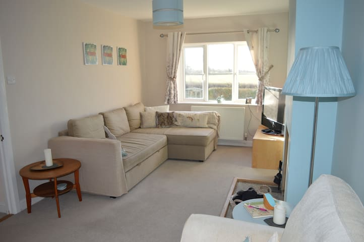 Bright and cosy lounge with large TV and DVD player