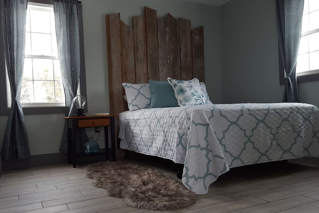 Bedroom - modern meets rustic with this comfortable queen bed and original one-of-a-kind hand-made barn-board headboard.  Smart TV in bedroom where you can access Netflix. Ensuite bathroom separated by sliding barn-track door. Walk-in closet for plenty of storage space.