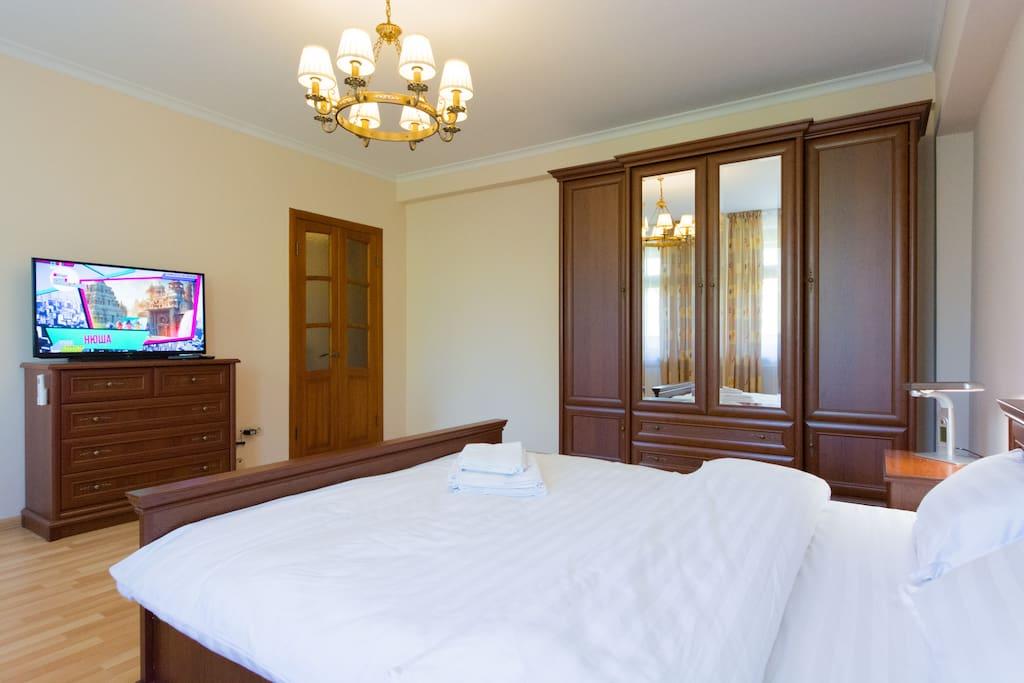Шкаф для одежды и телевизор с плоским экраном в спальне