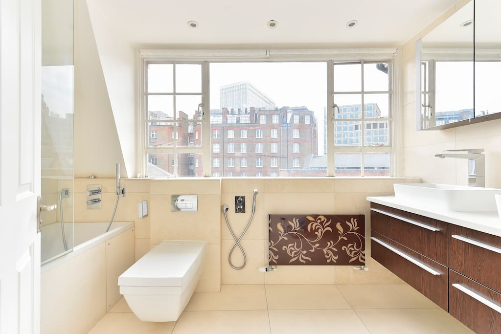 Large light bathroom with bath, shower and double sink.