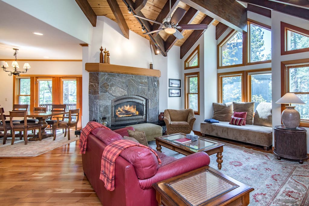 An oversized fireplace, vaulted wood ceiling, and a wall of windows accents this comfortable living space.