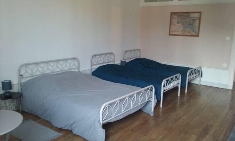 Chambre avec un lit double et deux lits simples