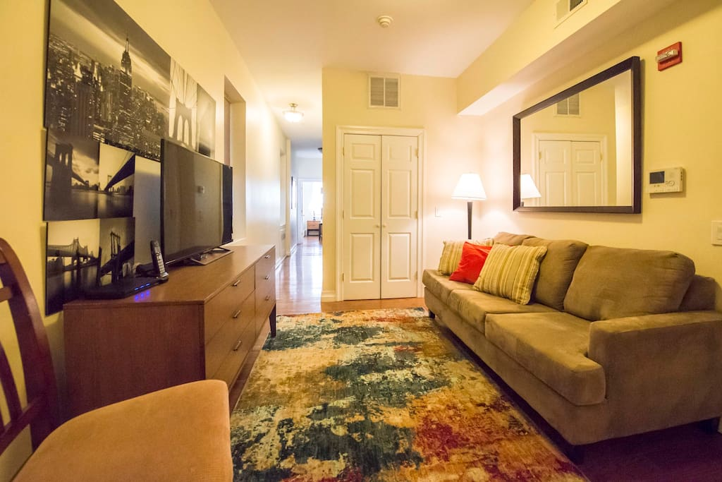 """Living room with 50"""" flat screen TV and full size sleeper sofa"""