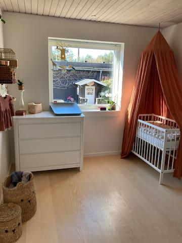 Børneværelse med en tremmeseng. Ved behov har vi dobbelt luksus luftmadras til 2 voksne som kan være i værelset.
