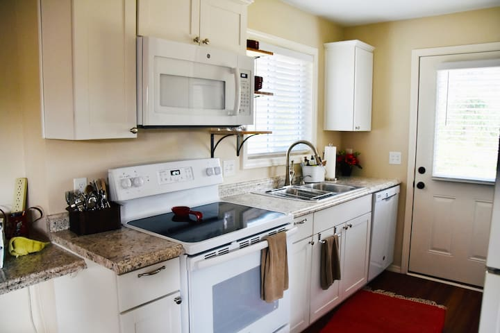 The kitchen has a microwave, electric range, full fridge, coffee/tea station, and washer/dryer, which has access to the private patio in the backyard.