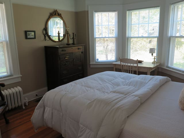 The downstairs bedroom, just down the hall past the bath, with queen size bed, writing desk and views of the yard and apple tree.