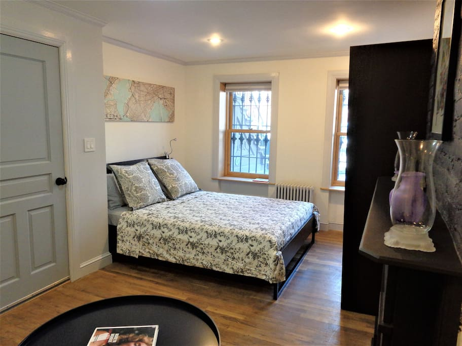 Bright, spacious first bedroom has large windows that bathe the space in daylight, and a queen-size bed that comfortably sleeps 2 guests.