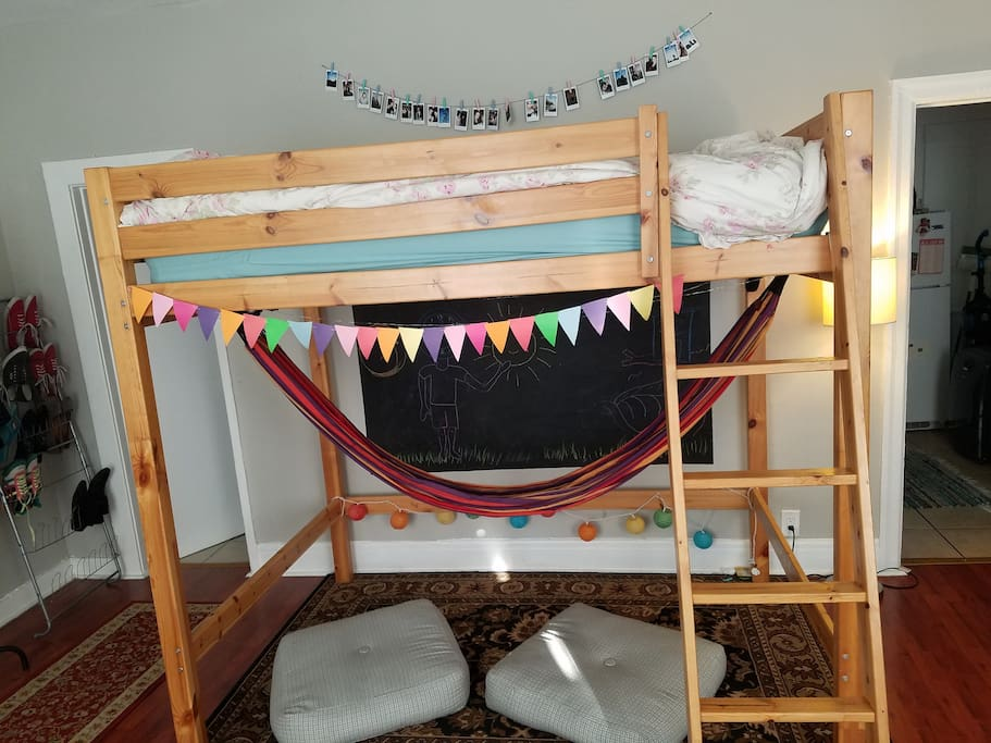 Lofted bed with hammock underneath and floor pillows