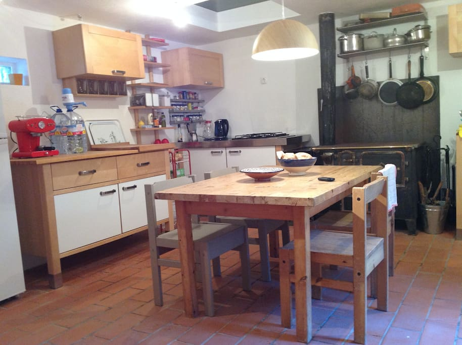 fully equiped kitchen and living room with traditional oven and cookingequipment.