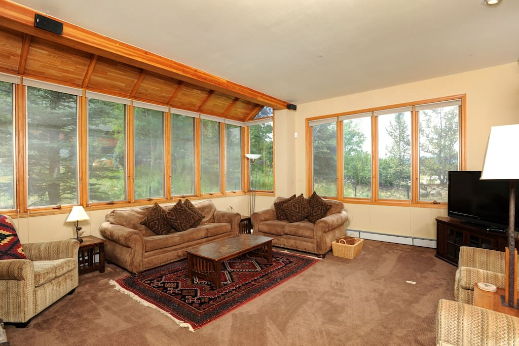 The living area features comfortable sofas and a TV