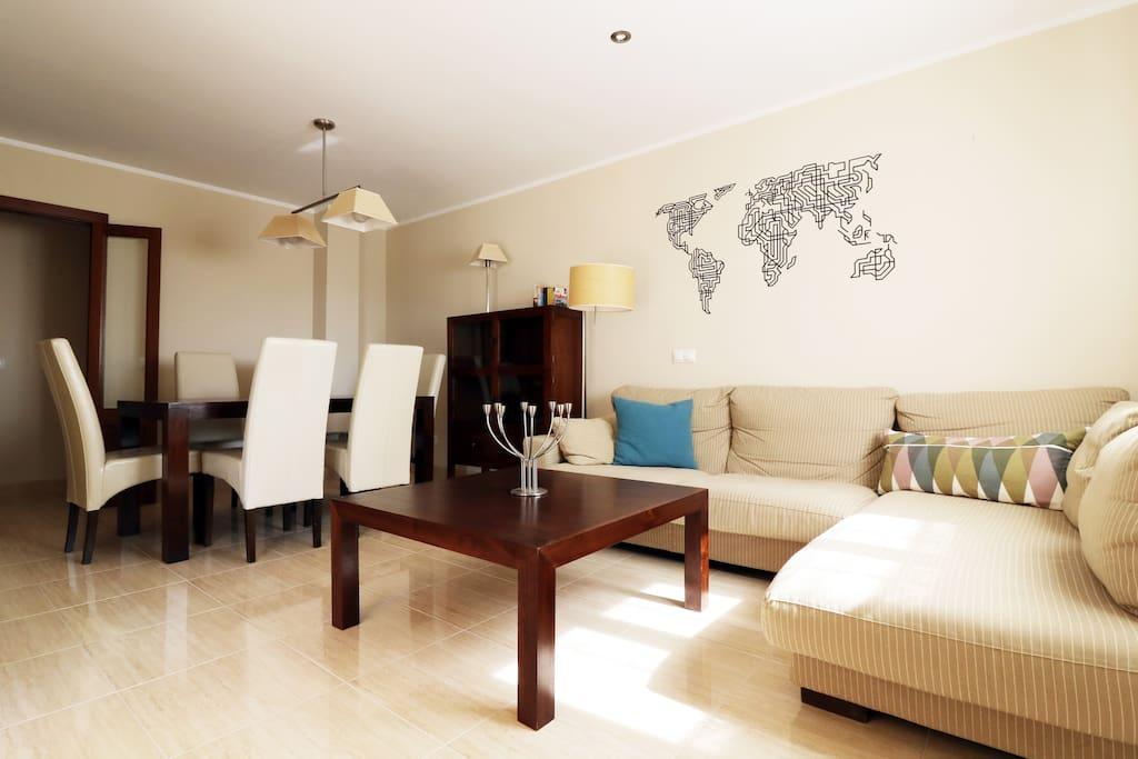 Wohn-/Esszimmer mit gemütlicher Couch und Esstisch mit Platz bis zu sechs Personen.