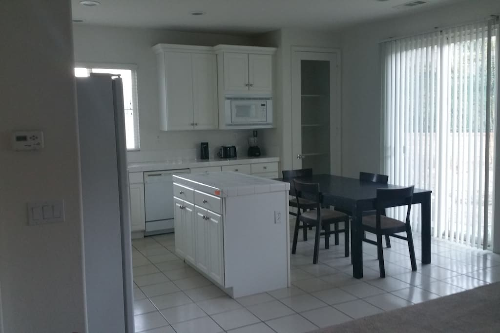 Kitchen,  Island, pantry, microwave, stove,  refrigerator, and table
