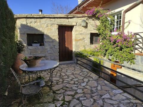 Casita de piedra con chimenea, jardín y barbacoa