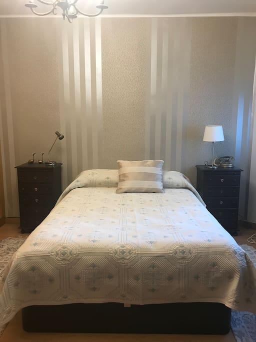 Habitación con Cama de 135 cm, colchón muy confortable, perfecta para dos personas. Espacio acogedor: pared empapelada, tarima de madera en el suelo y alfombras.
