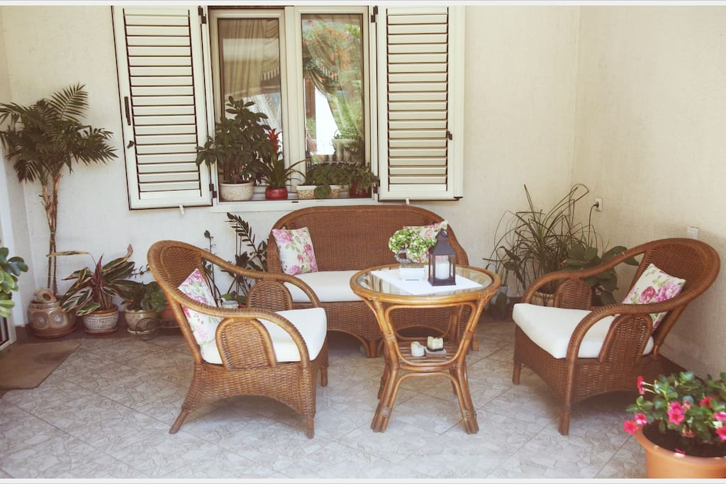 1st Floor: Large terrace with bamboo sofa set and Italian tiles surrounded by Mediterranean plants.