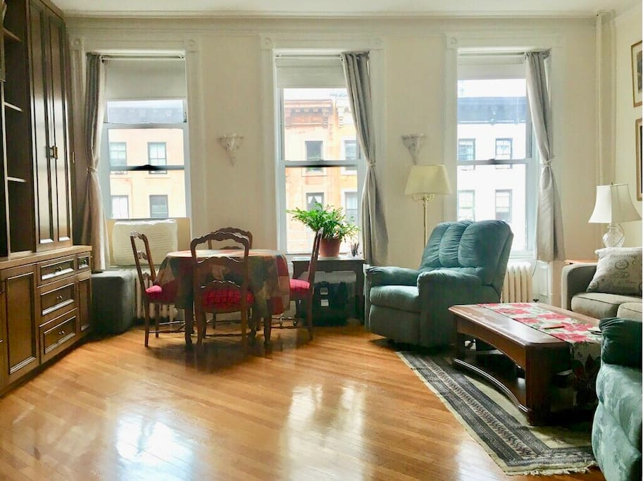 View of the living room, windows face Lexington Avenue.  Radiators by the windows control the heat and air conditioner in the left window is used in summer time.  Coach to the far right is the queen size pullout sofa. Bathroom to the left, one of two bathrooms in the apartment. Dining table can expand to seat 8.