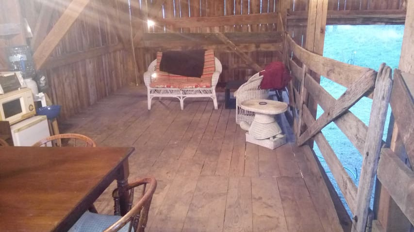 The living room of The Loft.  Views out the double barn doors at both ends of the barn.  Seats 3 comfortably