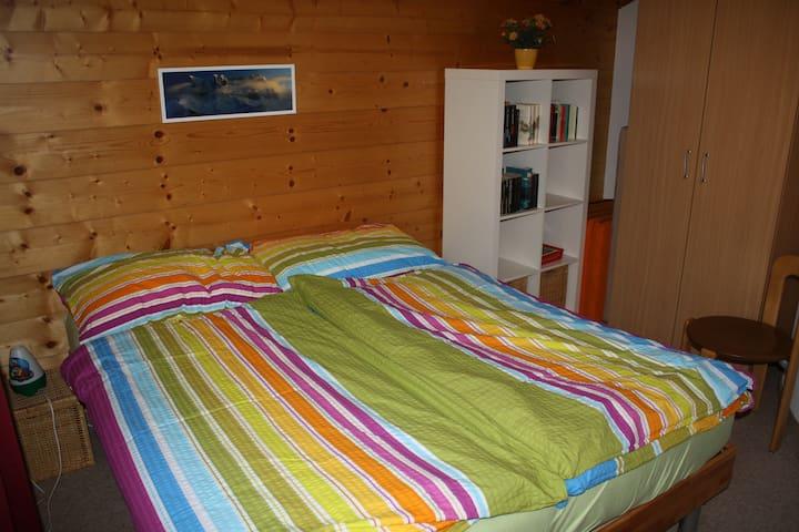 Schlafzimmer mit zwei Einzelbetten, die zusammengestossen werden können und einem Etagenbett. Kleine Bibliothek.