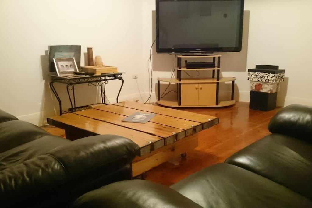 industrial look lounge, leather chairs with large TV and sound system