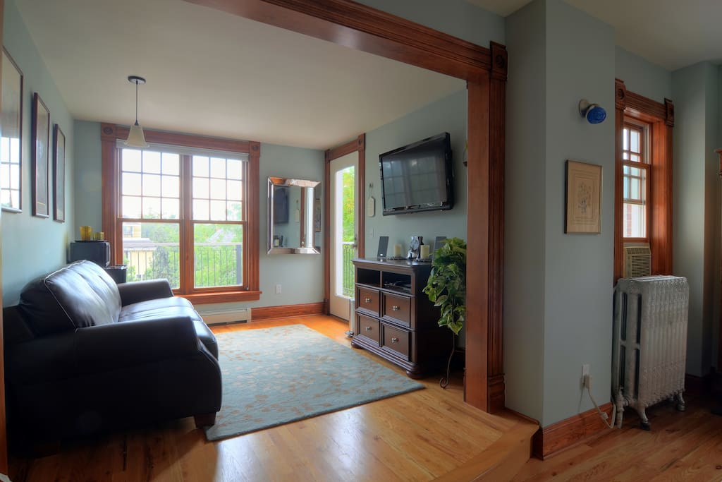 Sitting room with leather couch, wide-screen TV, cable, MP3 dock, mini-fridge and microwave.