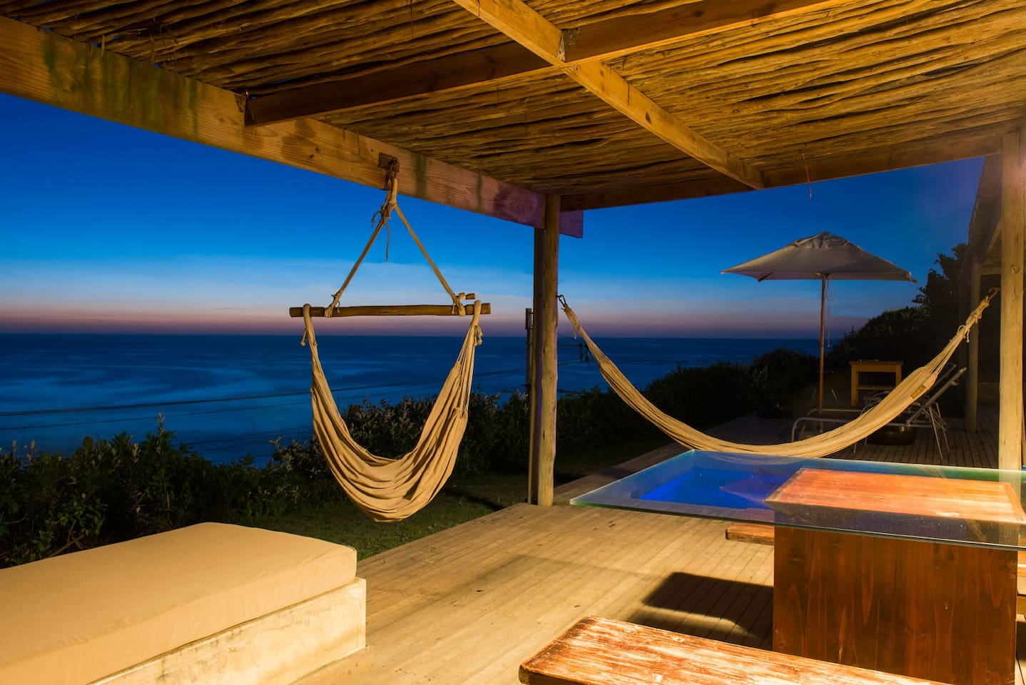 Front wrap around veranda View with hammocks and solar heated plunge pool.