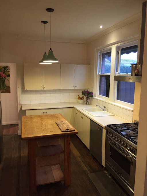Light and airy kitchen with stovetop, large stainless steel oven, dishwasher and fridge