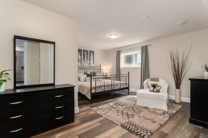 Master bedroom complete with comfortable king bed, dresser and blackout curtains. Snuggle up on cozy chair and ottoman in front of electric fireplace