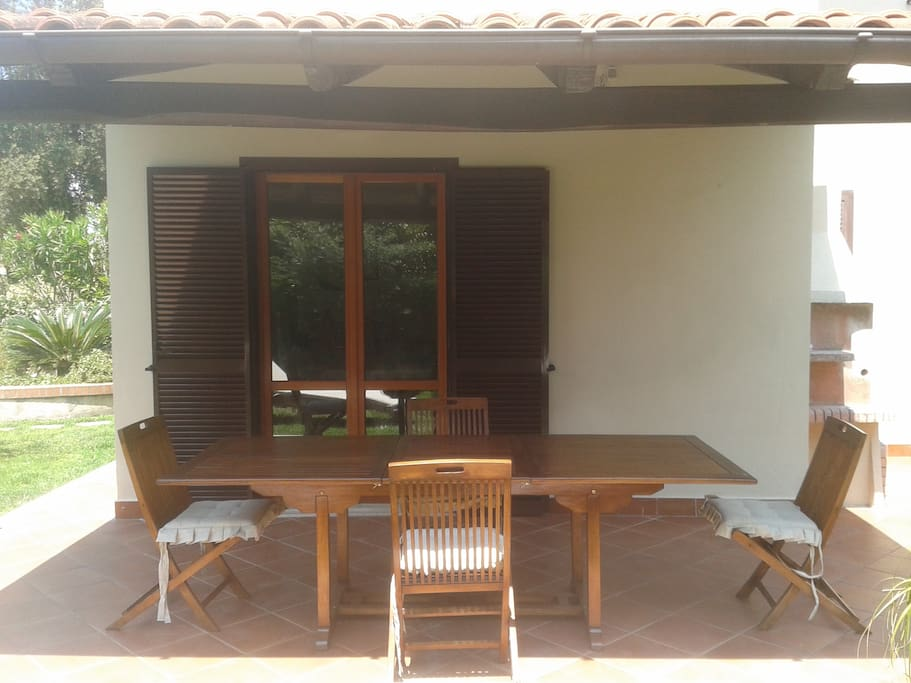 Patio esterno con tavolo allungabile e sedie.
