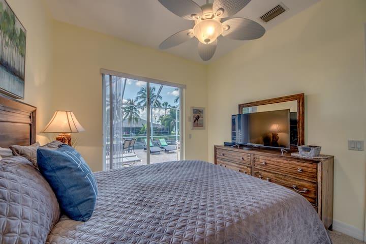 Guest bedroom with sliding glass door to pool. Flat screen TV