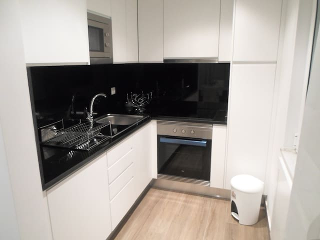 Kitchen with granite tops, fridge, freezer, microwave, stove and oven