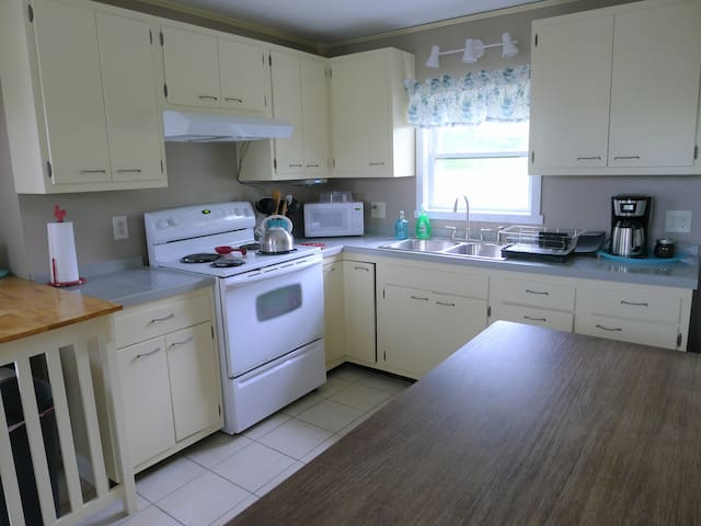 Kitchen has full size oven, range and range hood. The kitchen is fully stocked with dishware, bakeware and cookware.