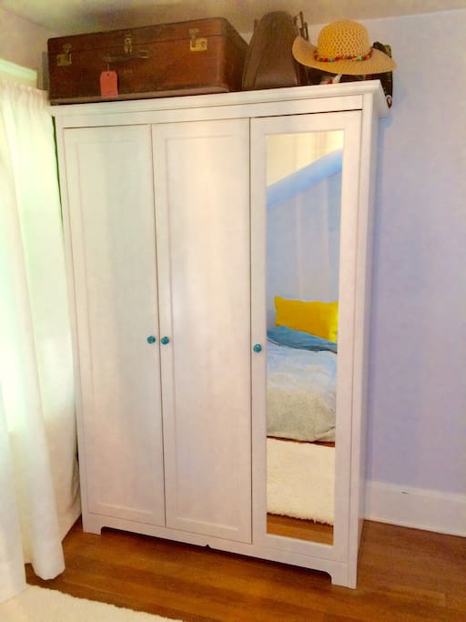 Armoire with shelves and rod for hanging clothing.