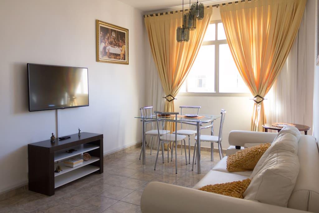 O Sofá de três lugares vira uma cama de solteiro. TV LED Full HD e mesa de jantar para 4 pessoas