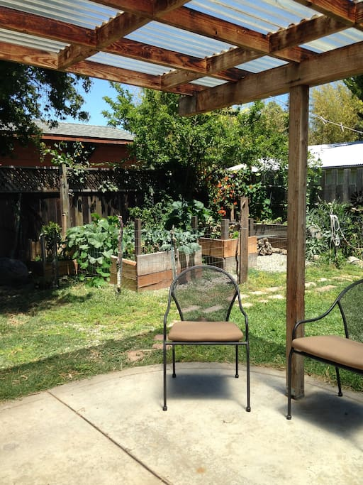 Patio and shared backyard with vegetable garden and fruit trees.