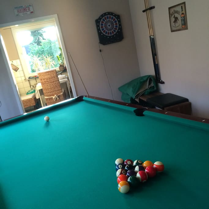 Großer Billardtisch und Dartscheibe laden im offenen Wohnzimmer zum Spielen ein