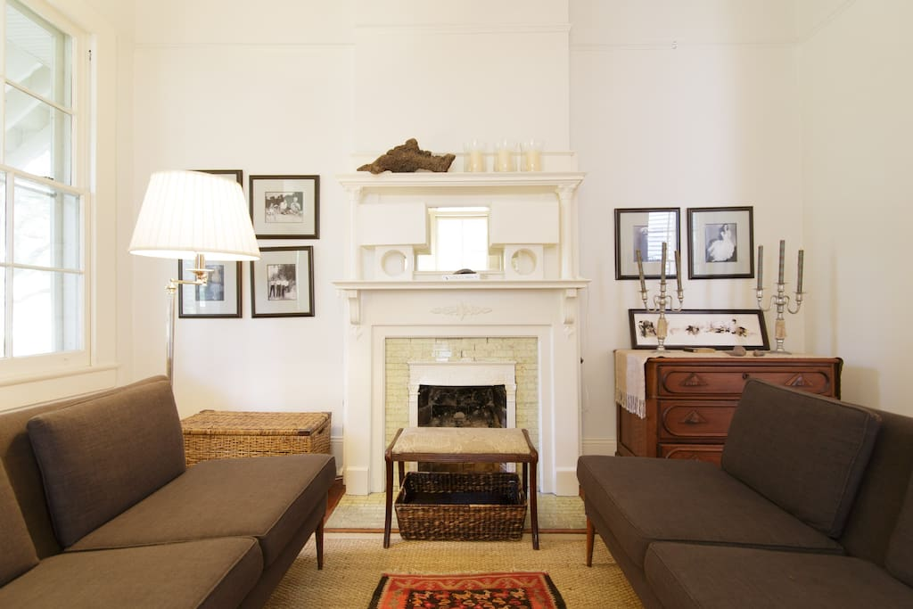 In the front room a pair of Paul McCobb settees flank the original (non-working) fireplace.
