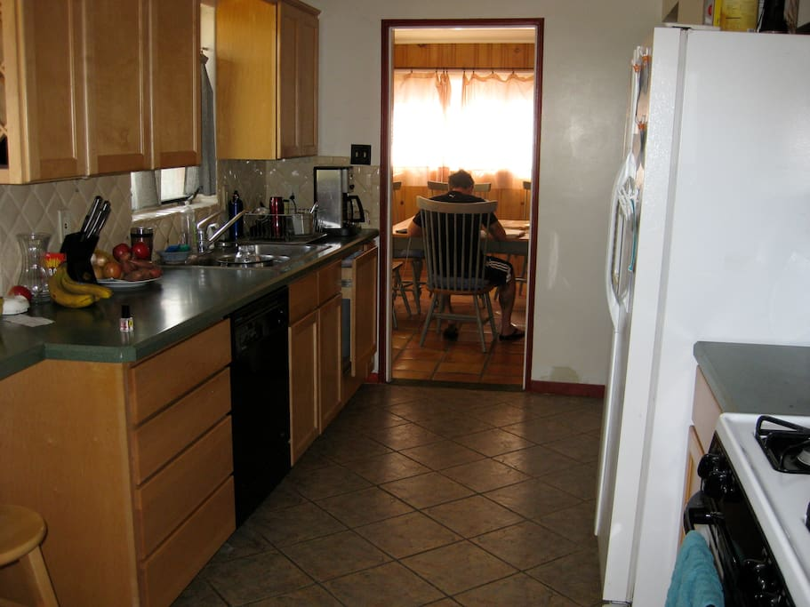 Clean kitchen with everything you need. Study area as well! That is a guest using the dining room for studying.