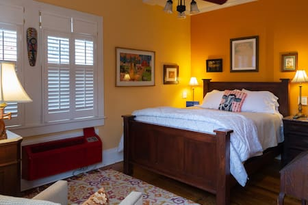 a small but very cute room with a queen bed